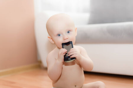 baby sitting on wooden floor and playing mobile phone with touch screen photo