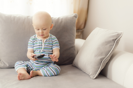 baby uses a remote control for tv at the sofa photo