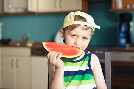 baby 4 5 years: 5 year old happy boy eats a watermelon at the kitchen table Stock Photo