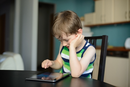 baby 4 5 years: preschooler play games on the tablet at home