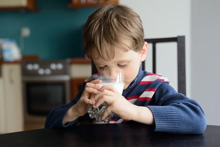 politely: preschooler politely drinking the milk at the table - indoors