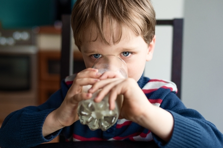 preschooler  drinking the milk at the table - close up