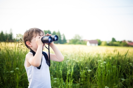 little boy in a field looking through binoculars - sunny day Banco de Imagens