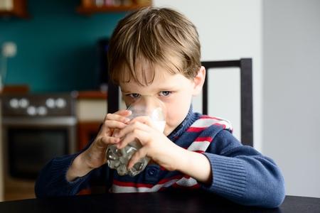 kid boy drinking milk at kitchen table photo