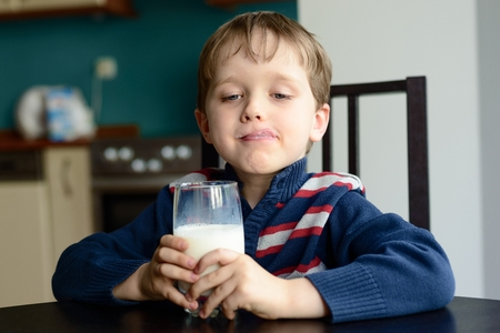 Boy with glass of delicious  milk at home photo