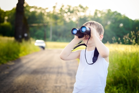 schoolkid search: Little boy looking through binoculars while walking on a rural road Stock Photo