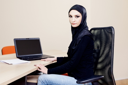 wearer: Muslim hijab wearer woman sitting at a desk with a computer at the office