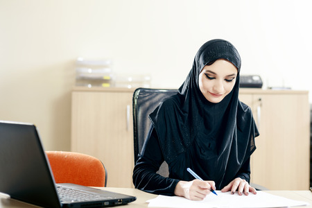 arab adult: Muslim woman fills the documents while working in the office Stock Photo