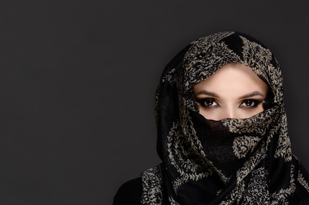 Beautiful Woman in Middle Eastern Niqab veil on grey background photo