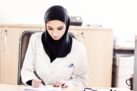 femmes muslim: Femme m�decin musulmane remplit les dossiers m�dicaux de assis � un bureau