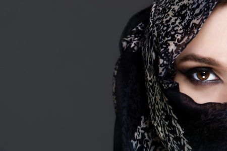 middle adult: Beautiful girl wearing a niqab - grey background