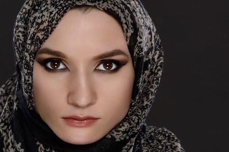 arab model: Portrait of a front view of a beautiful arab woman face with a head scarf on a gray background Stock Photo