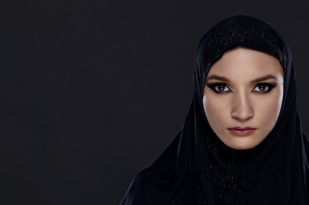 Close portrait of a beautiful Muslim woman dressed in black hijab on a gray background