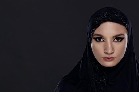 femmes muslim: Fermer portrait d'une belle femme musulmane v�tu de noir hijab sur un fond gris Banque d'images