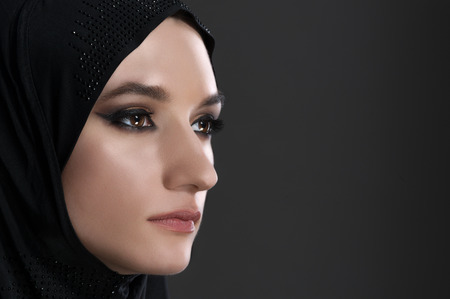 arab hijab: pretty young muslim woman head shot over gray background