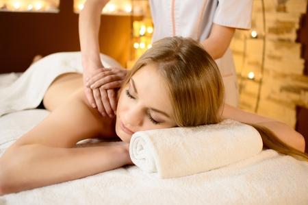 massage: Belle jeune femme blanche couch�e sur une table de massage et est mass� Banque d'images