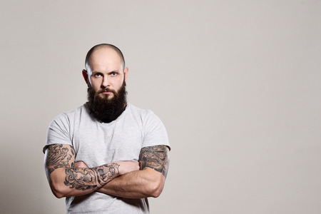 tattoo arm: Bearded man with crossed arms - studio shot