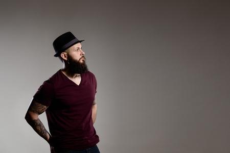 hombre con barba: joven hombre con barba inconformista que lleva el sombrero - fondo gris