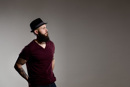 hairy male: young hipster bearded man wearing hat - gray background