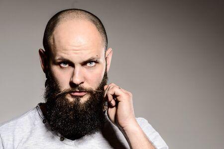 hombre con barba: Primer del hombre barbudo tocar la barba mientras est� de pie contra el fondo blanco