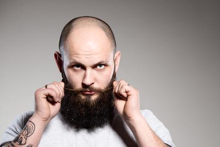 hombre barba: hombre con barba que toca la barba - fondo gris Foto de archivo