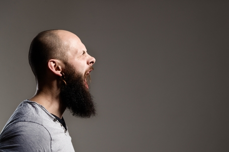 man face profile: Side view portrait of screaming bearded man - gray background