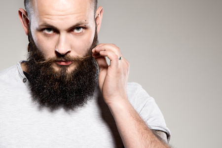 funny bearded man: bearded man touching mustache - grey background Stock Photo