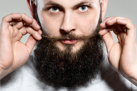 funny bearded man: man with beard adjusting his mustaches while standing against grey background