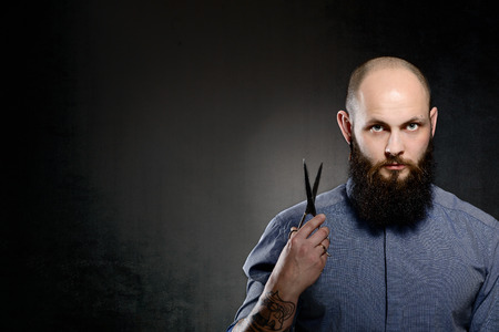 Bald man with a beard wearing a blue shirt is holding a pair of scissors Stock Photo