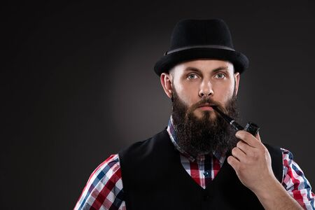 Bearded man in a checkered shirt and a hat smoking a pipe photo