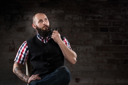 Thoughtful bearded man in a checkered shirt smoking a pipe sitting in front of a brick wall photo