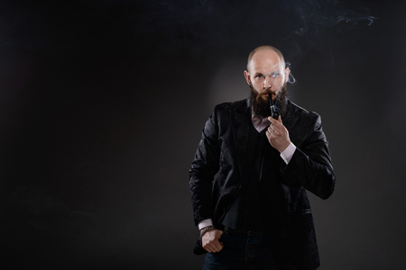 Bearded bald elegant man smoking a pipe on a gray background photo