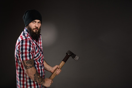 Muscular lumberjack holding a old used ax. He has a lush beard and tattoos on his arms. He is dressed in a checkered shirt and a black cap. He looks toward the lens.