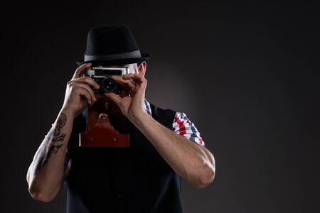 regulate: Hipster wearing a checkered shirt, takes a photo of an old camera. His fingers regulate focus. He wears a black hat. His hands are decorated with tattoos.