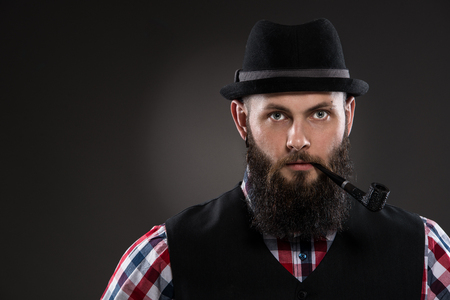 Muscular tattooed man holding a pipe in his mouth. He wears a black hat. He is dressed in a checkered shirt and a black vest. Gray background. photo