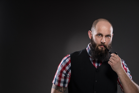 Muscular tattooed man smokes a pipe. He is dressed in a checkered shirt and a black vest. Gray background. photo