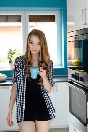 Happy blonde woman holding a cup of coffee in her kitchen. Standing in front of a window in the kitchen, next to the oven and microwave photo