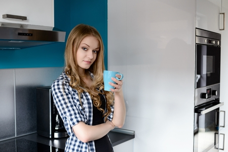 Beautiful blonde woman drinking coffee in the kitchen. She leans against the a kitchen cabinet. In the background you can see a microwave and oven. photo