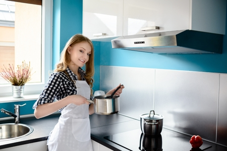 Beautiful blonde woman cooking in the modern kitchen. Checks the taste of the dish - it probably tastes good - she is smiling