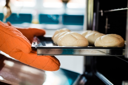 Baker hands with potholder next to metal cookie sheet with bread in oven