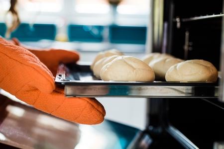Baker Hände mit Topflappen neben Metall Backblech mit Brot im Ofen Standard-Bild
