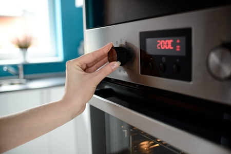 Close up of womans hand setting temperature control on oven. The display shows the set temperature to 200 degrees Celsius