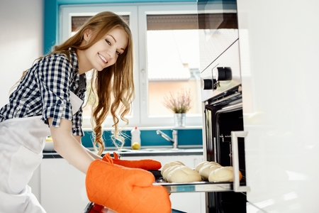 woman baking: caucasian woman baking a bread in kitchen oven. She pulls rolls from the oven. Hands protected by orange kitchen gloves.