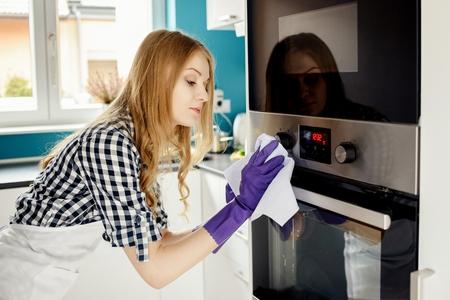 haushaltshilfe: Sch�ne blonde Frau, Polieren von Edelstahl Ofen. Auf ihre H�nde Schutzgummihandschuhe.