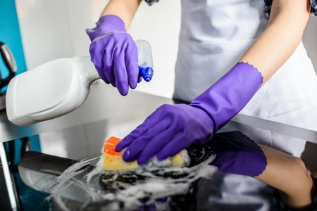 Woman's hands cleaning kitchen top in rubber protective gloves