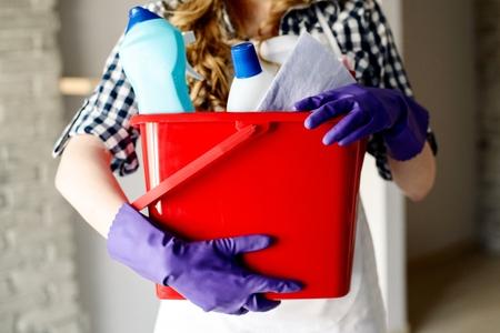 trabajando en casa: Primer plano de manos de la mujer la celebraci�n de cubo de color rojo lleno de productos de limpieza