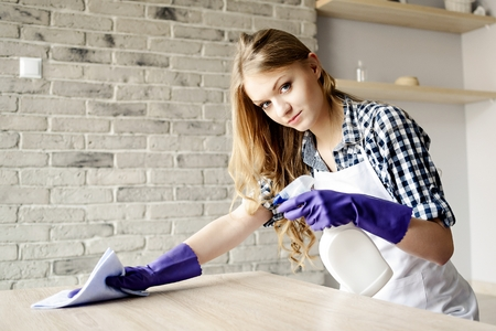Smiling long-haired blond woman cleaning table at home. She is wearing a white apron. On hands has protective rubber gloves Stock Photo