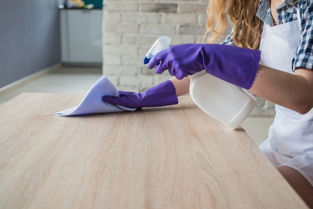 Female hands cleaning table in the living room. On hands protective rubber gloves