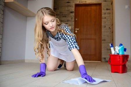 knee pads: Beautiful young woman washes the floor on her knees. On hands has protective rubber gloves. Behind her, a bucket of cleaning utensils. Stock Photo