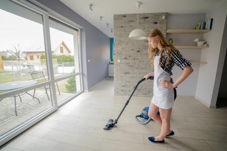 Beautiful blond woman vacuuming living room. She is wearing a white apron